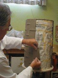 Lavorazione portaombrelli: fase dell'applicazione del rettangolo in argilla su sagoma tubolare rivestita di carta