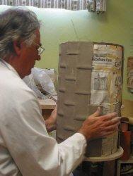 Lavorazione portaombrelli: fase della schiacciatura del rettangolo in argilla su sagoma tubolare rivestita di carta