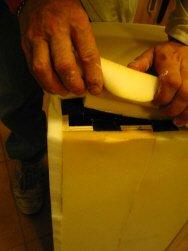 Lavorazione del pouf: fase della gomma piuma sulla struttura di legno, con visibili le cinghie